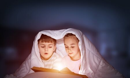 Engrossed little girl and boy reading book in bed after bedtime. Pretty kids together hiding under blanket. Preschool children in pajamas reading fairy tales. Bedroom with deep blue sky background