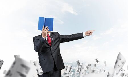 Businessman covered his face with organizer and finger pointing side. Man in business suit and tie standing on cityscape background with falling paper documents. Education and professional knowledges.