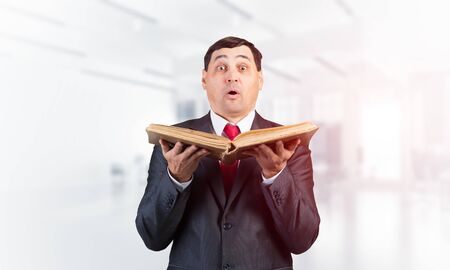 Surprised businessman holding open book and looking at camera. Startled adult man in business suit and tie standing on blurred office background. Education and knowledges. Business accounting service