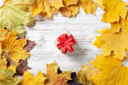 Flat lay cute composition with gift box and yellow autumn leaves. Holiday present decorated red ribbon bow on vintage wooden desk. Happy thanksgiving congratulation. Still life of autumn season.