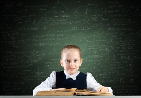 Smiling little girl sitting at desk with open book. Research and education in school. Happy schoolgirl studying in library. Clever girl in schoolwear reading book on chalkboard background.