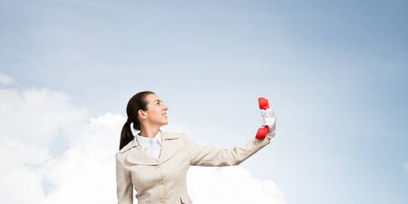 Businesswoman holds vintage red phone on distance. Telemarketer in business suit with telephone looks upward on blue sky background. Employee ignores communication. Business assistance and support