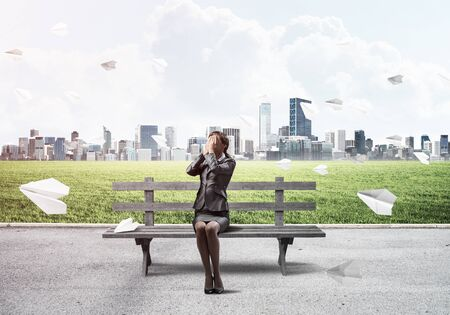 Young woman sitting on wooden bench outdoors. Girl in business suit keeps hands on face for surprise. Hide from problems. Help and successful solutions. Cityline panorama with flying paper planes.