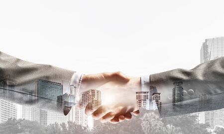 Close of business people shaking hands as symbol for partnership. Mixed media