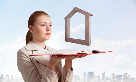 Woman with house sign above opened notebook. Architecture agency advertising. Sale and rent new real property. Elegant young woman in white business suit on background of cityscape and blue sky.