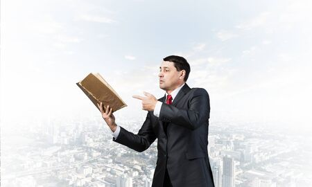 Senior businessman finger pointing into open old book. Portrait of adult man in business suit and tie standing on cityscape background. Manager holding big handbook. Professional reference information