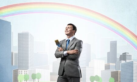 Confident and creative businessman painter standing with arms folded. Happy handsome man in business suit and tie holding paintbrush on city background. Cityscape illustration with colorful rainbow.