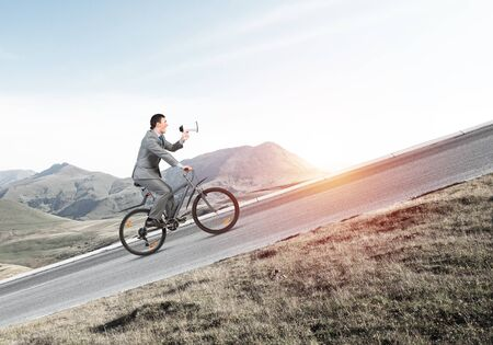 Businessman with megaphone in hand on bike at sunny day. Promotion and announcement. Corporate employee in business suit on bicycle riding uphill on mountain road. Cyclist on background of blue sky
