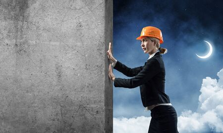 Beautiful woman architect pushing concrete wall. Young specialist in safety helmet on night sky background. Engineering and development company. Overcoming obstacles and solution of problems.