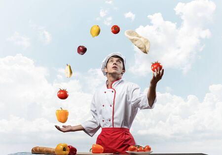 Young male chef juggles with food ingredients. Handsome chef in white hat and red apron on blue sky background. Professional cooking classes advertising. Food retail campaign announcement.