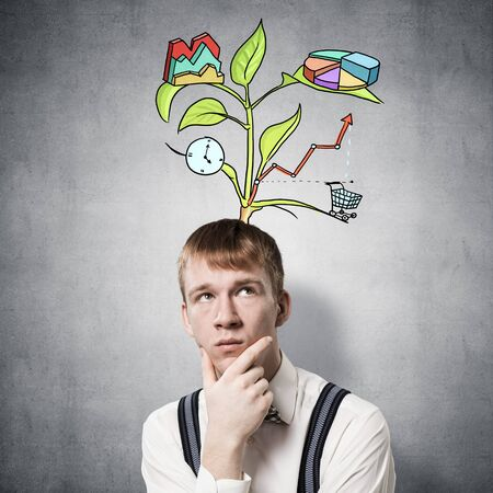 Redhead student looks pensive upwards and thinking about some genius idea. Clever boy with drawing ideas tree above head. Young scientist on background of grey wall. Idea generation process.