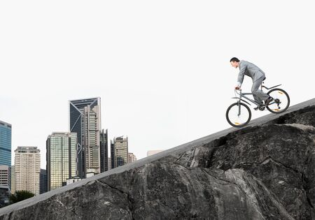 Businessman riding downhill by bike. Nature landscape with copy space. Man in business suit riding bicycle on mountain road. Cyclist on background of blue sky. Healthy lifestyle and outdoor activity