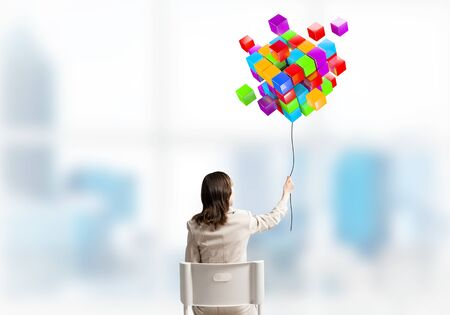 Woman holding by rope abstract colorful composition from 3d cubes. Back view long haired woman in white suit sitting on white chair in light office. Digital technology and innovation solutions. Banque d'images - 137185059