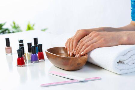 Mani femminili del primo piano in ciotola di legno con acqua. Procedura termale e relax. Mani femminili che si preparano per la manicure. Servizio professionale di cura delle unghie ed estetista. Concetto di bellezza e igiene