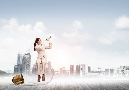 Attractive woman playing trumpet brass on background modern city. Young businesslady in white suit and gloves sitting on big light bulb with music instrument. Musician practicing and performing Stock Photo