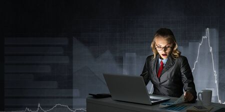 Surprised businesswoman in glasses sitting at office desk and working at laptop on background grey wall with chart. Female broker in business suit and tie busy at work in evening. Online stock trading