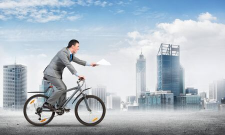 Businessman with paper documents in hand on bike. Courier with documents. Corporate employee in grey business suit riding bicycle on background of modern cityscape. Accounting and financial statements Archivio Fotografico