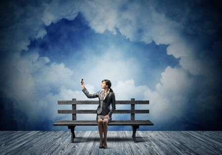 Young woman in business suit holding smartphone with raised hand. Girl with mobile phone sitting on wooden bench. Mobile marketing and digital technology. Beautiful skyscape with deep blue night sky Stockfoto