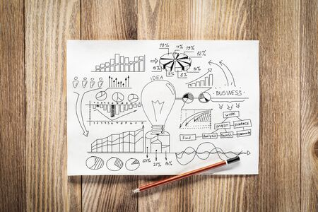 Business infographics pencil hand drawn with group of commercial doodles. Top view of workplace with paper and pencil lying on wooden desk. Financial statistics and analytics. Light bulb and charts