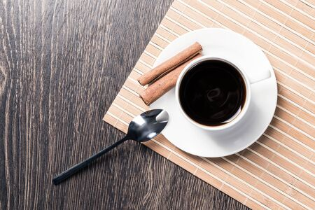 Cup of espresso coffee on wooden table. Top view white porcelain cup and cinnamon sticks on saucer. Close up fresh and aromatic hot drink in cafe. Morning coffee and break time concept. Stok Fotoğraf