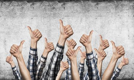 Row of man hands showing thumb up gesture. Agreement and approval group of signs. Human hands gesturing on background of grey wall. Many arms raised together and present popular gesture.