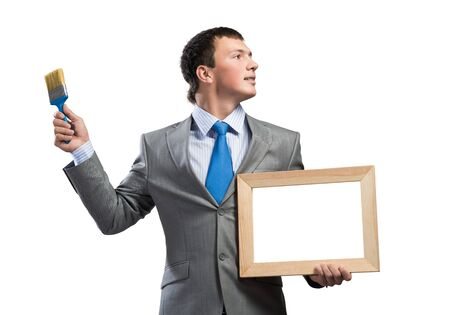 Creative businessman painter holding paint brush and whiteboard in hands. Portrait of handsome young man in business suit and tie isolated on white background. Inspiration and creativity in business.