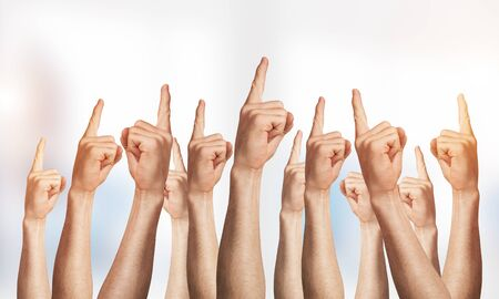 Row of man hands showing finger pointing gesture with forefinger. Group of human hands gesturing on light blurred background. Many arms raised together and present popular gesture. Banco de Imagens