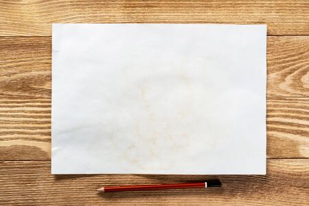 Sheet of paper lying on wooden table. Blank white a4 format paper with pencil. Space for writing and notification. Textured natural wooden background. Vintage copy space for creative design. Stock Photo