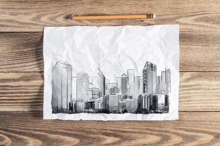 Big city skyline pencil draw. Modern downtown landscape with high skyscrapers sketch on wooden surface. Paper and pencil on textured natural wooden background. Real estate agency concept.