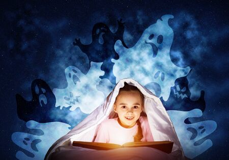Happy little girl reading book in bed before going to sleep. Child with flashlight hiding under blanket. Smiling girl in pajamas and funny ghosts back on night sky. Child reading magic fairy tales.