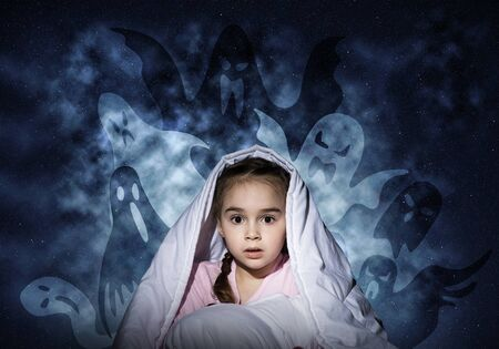 Scared girl hiding under blanket. Startled kid sitting in bed on night sky background. Little girl afraid of dark. Covered child not sleep at night. Fearful girl in pajamas and imaginary monsters.