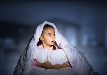 Scared girl with pillow hiding under blanket. Startled kid lying in his bed at home. Little girl afraid of dark. Covered child not sleep at night. Girl in pajamas on blue blurred background.
