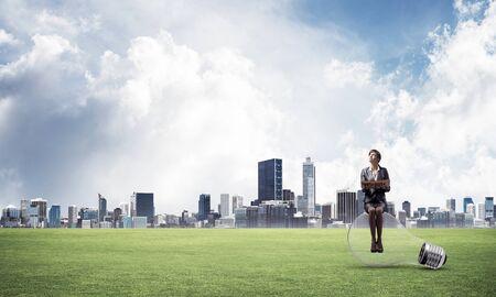 Mujer sonriente joven con libro abierto sentado en bombilla grande. Hermosa chica en traje de negocios en el fondo del paisaje con el centro moderno, la hierba verde y el cielo azul. Educación y creatividad.