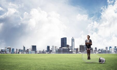 Young smiling woman with open book sitting on big light bulb. Beautiful girl in business suit on background of landscape with modern downtown, green grass and blue sky. Education and creativity.