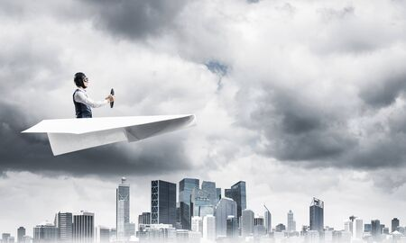 Businessman in aviator hat and goggles driving paper plane in storm. Crisis management concept. Side view of pilot in small paper airplane. Megalopolis panorama with dramatic dark cloudy skyscape.