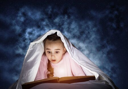Engrossed little girl reading book in bed before going to sleep. Pretty kid with flashlight hiding under blanket. Beautiful girl in pajamas on deep blue sky background. Child reading fairy tales.