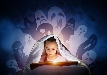Engrossed little girl reading book in bed after bedtime. Kid in pajamas with flashlight hiding under blanket. Fearful girl and imaginary monsters on deep blue background. Child reading fairy tales. Banco de Imagens