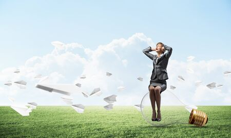 Young woman sitting on light bulb. Girl in business suit keeps hands on face for surprise. Businesswoman playing hide and seek on green meadow with flying paper planes. Help and successful solutions