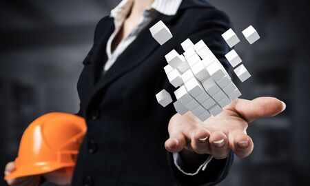Businesswoman holds in palm abstract 3d cube model. Woman engineer in business suit with orange safety helmet. Engineering and project management. Architecture and construction company presentation