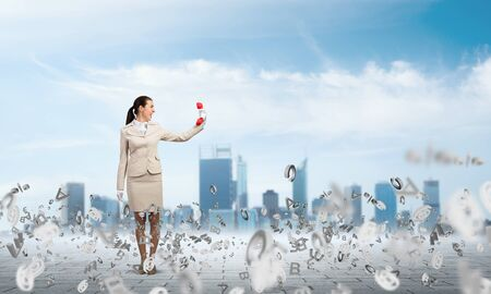 Woman with red phone on background modern cityscape. Elegant secretary with telephone and flying various letters around. Business assistance and support concept. Information flows and management