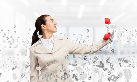 Woman keep at distance vintage red phone. Elegant operator in white business suit posing with landline phone in office with flying various letters. Hotline telemarketing and business communication.
