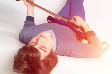 Young man with closed eyes practicing electric or bass guitar. Guitarist lying back on white sofa. Close-up caucasian musician in sweater and jeans playing acoustic guitar. Playing musical instruments Banque d'images - 138758573