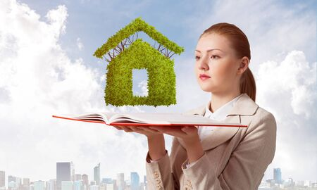 Woman with green plant shaped house above opened notebook. Real estate agency advertising. Sale new real property. Elegant young woman in white business suit on background of cityscape and blue sky.
