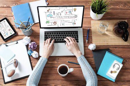 Concepto de educación multimedia con espacio de trabajo de oficina. Escritorio de madera plano con laptop, manos de mujer y taza de café. Mujer de negocios trabajando en maqueta de computadora. Seminario web en línea o webcast de la conferencia