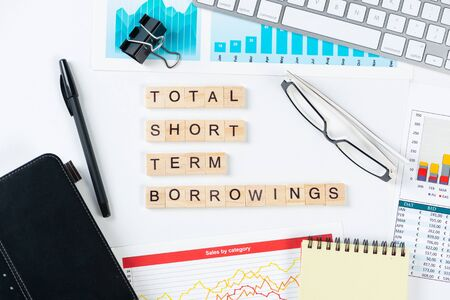 Total short term borrowings concept with letters on cubes. Still life of office workplace with supplies. Flat lay white surface with notepad, pen and financial report. Capital management and banking.