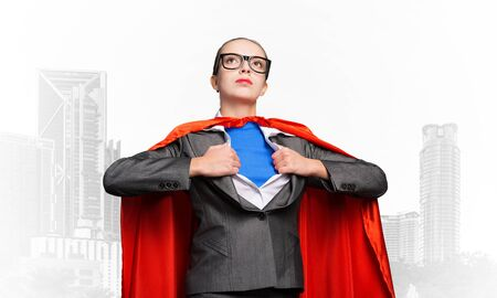 Beautiful business woman opening her shirt like a superhero. Confident lady in glasses with red hero cape. Brave super woman ready for new wins. Woman wears superhero t-shirt under her business suit. Standard-Bild
