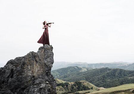 Junges attraktives Mädchen, das Geige spielt, das an der Spitze des Felsens steht