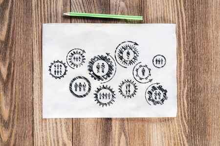 Corporate social responsibility concept with group of rotating gears and cogs. Human resources cooperation sketch on wooden surface. Workplace with paper and pencil lying on wooden desk. Stock Photo