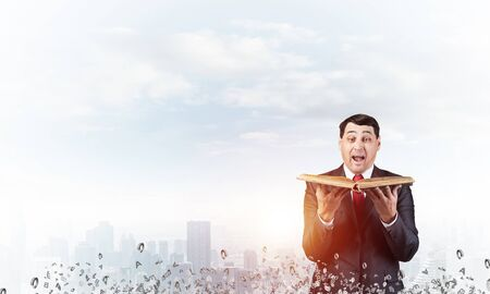 Surprised businessman holding book with open mouth. Joyful adult man in business suit and tie standing on cloudy cityscape background with flying various letters. Business education and knowledges.