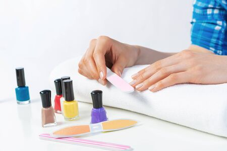 Woman using nail file and create perfect nails shape. Colorful nail polish bottles on table. Grinding female nails with nail file. Woman doing herself nail care procedure at home. Beauty and hygiene